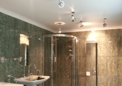 Waterproof plaster fitted in a bathroom. Note the cut outs for the newly wired spot lights.