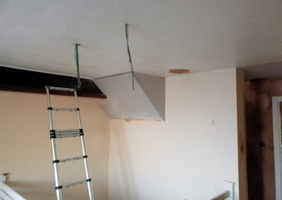 Cut and shaped plasterboard being fitted underneath a stairwell ahead of the new plaster being applied.